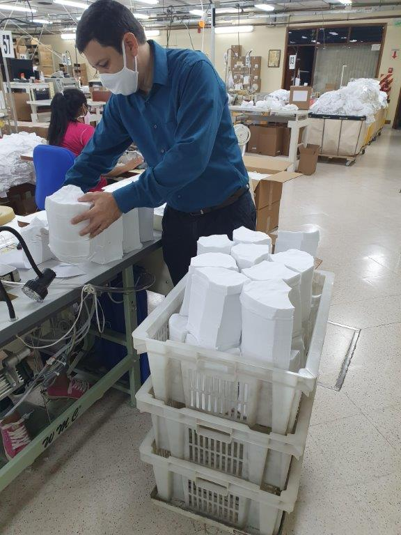 A Beehive Clothing employee transfers a pile of pre-cut mask material to baskets in mid-May 2020, in Luque, Paraguay. Four Beehive Clothing locations outside of the United States, including the Luque location, closed during the COVID-19 outbreak but were reopened after local governments allowed the Church to use the plants to sew masks for the community.