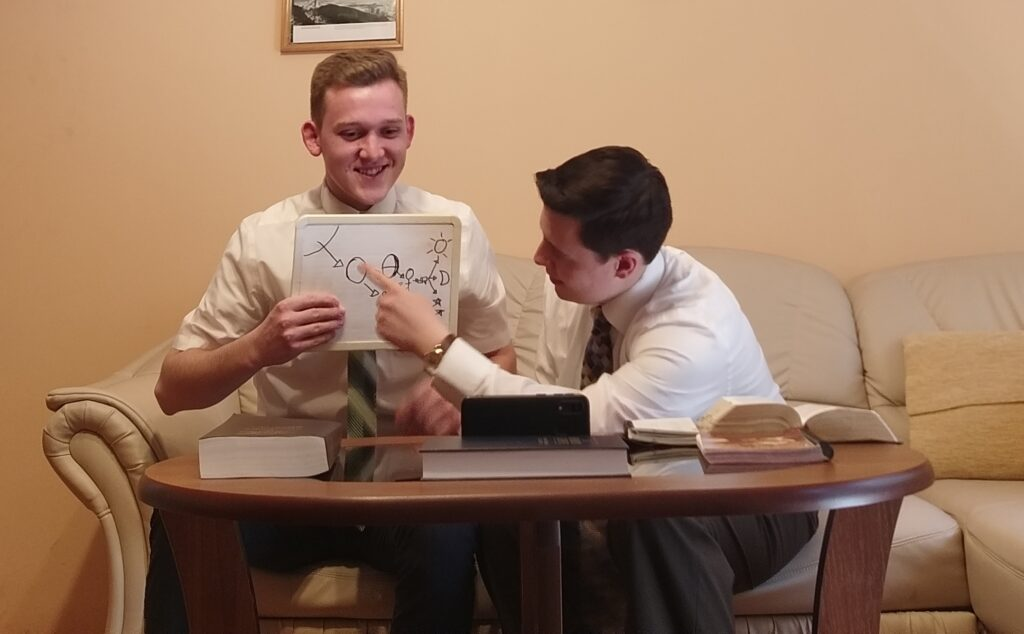 Elders Cole Brooks, left, and Hunter Strobel of the Hungary/Romania Mission use a visual aid in teaching via a smartphone in May 2020 from their Nyiregyhaza, Hungary, apartment.
