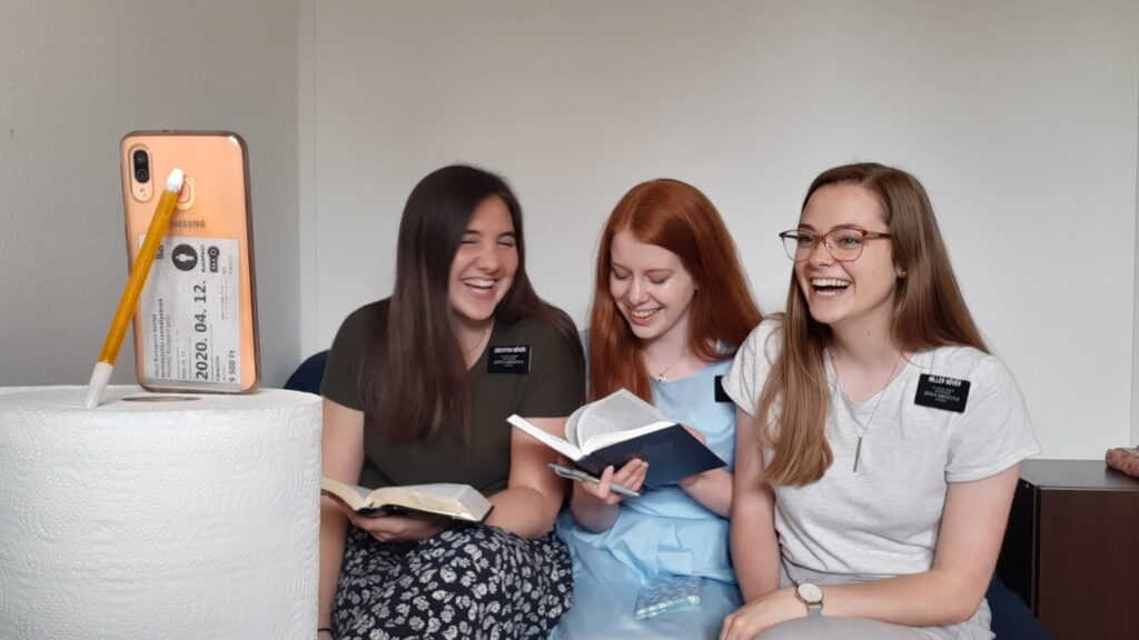 From left to right, Sisters Gabrielle Usevitch, Raquel Wilson and Alison Miller of the Hungary/Romania Mission share a laugh during an online interaction via smartphone in their Kispest, Hungary, apartment in May 2020.