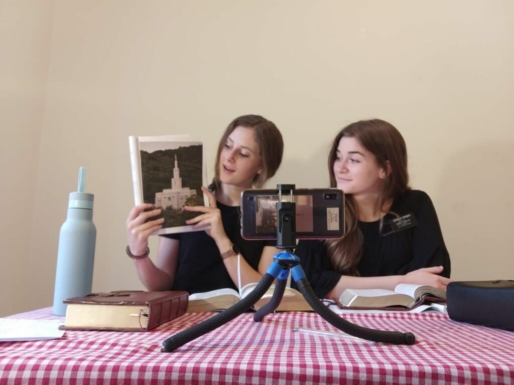 Sister Lindsey Schmidt, left, and Sister Elise Winger of the Italy Milan Mission teach an investigator via a smartphone in Bologna, Italy, in May 2020.