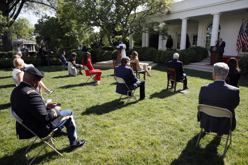 President Donald Trump listens as Sister Eneyda Martinez, with Poor Sisters of St. Joseph, at left podium, speaks during a White House National Day of Prayer Service in the Rose Garden of the White House, Thursday, May 7, 2020, in Washington.