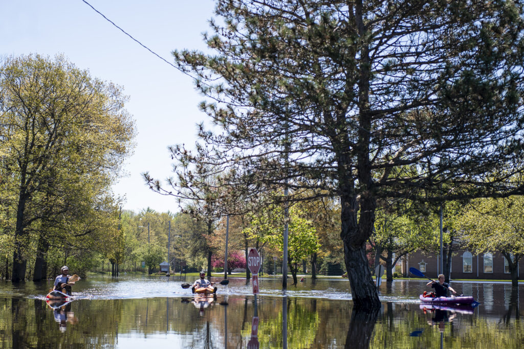 People kayak over the flooded Main Street near H. H. Dow High School in Midland on Thursday, May 21, 2020. The Edenville Dam failed on Tuesday, May 19 and caused the Tittabawassee River to flood many area throughout Midland. (Kaytie Boomer/The Bay City Times via AP)