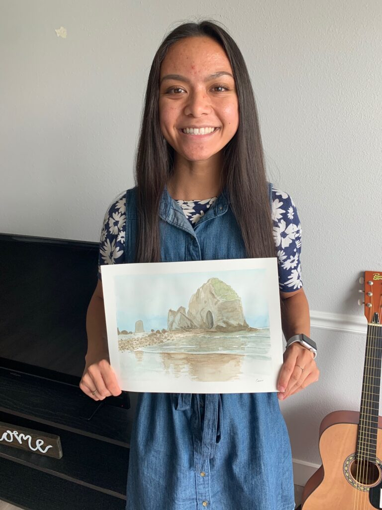 BYU student Cami Morata holds up her favorite picture she has painted — Cannon Beach in Oregon.