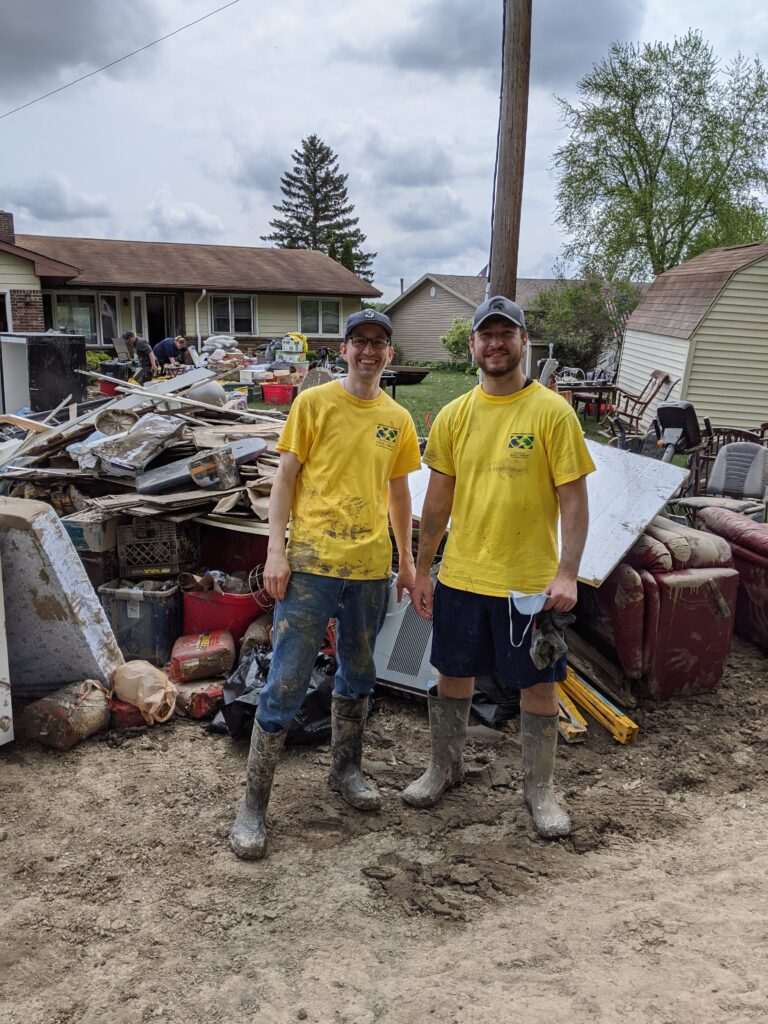 Two Helping Hands volunteers standing in front of the items hauled from a home in Midland, Michigan.