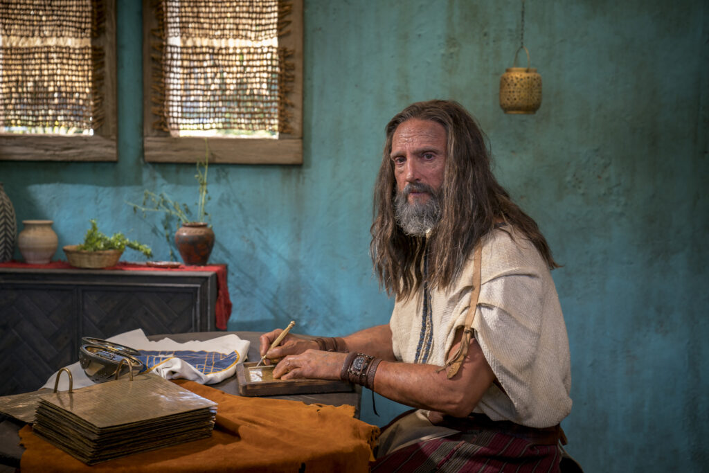 An actor portraying Nephi in the Book of Mormon Videos sits at a table with the brass plates and metal plates as he records his testimony.