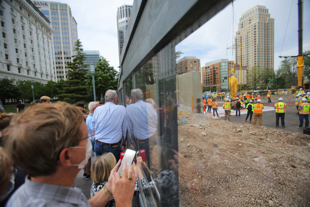 Onlookers gather at the fence to get a closer look of the Angel Moroni statue after workers from Jacobsen Construction removed it from the Salt Lake Temple of The Church of Jesus Christ of Latter-day Saints in Salt Lake City on Monday, May 18, 2020.The temple is currently undergoing renovation.