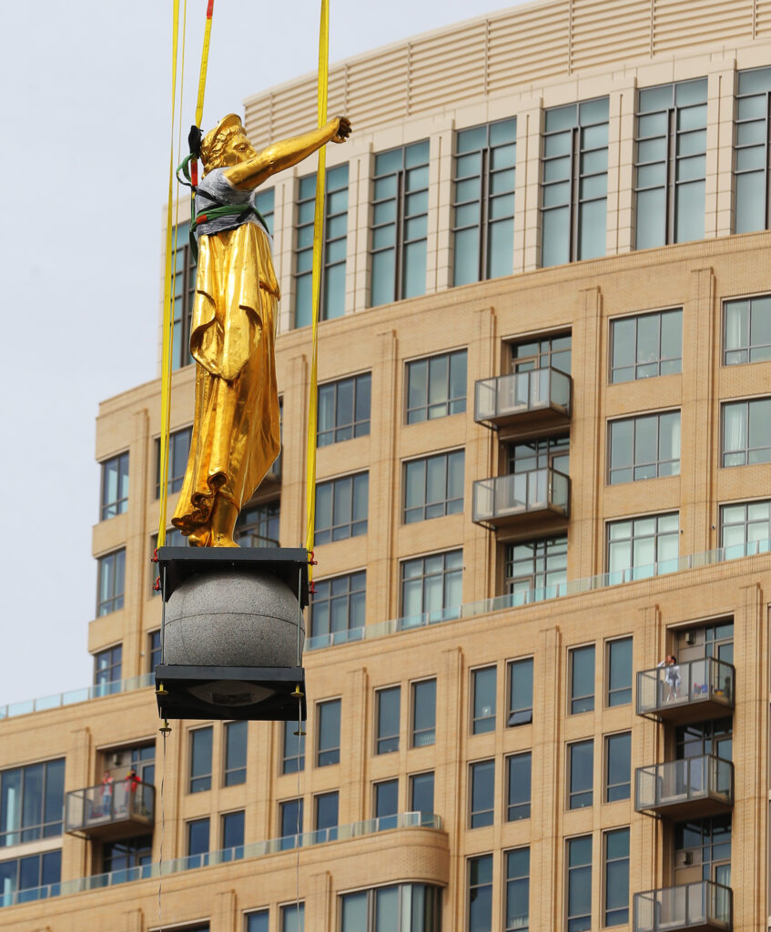 The Angel Moroni statue is carefully lowered to the ground by workers from Jacobsen Construction after they removed it from the Salt Lake Temple of The Church of Jesus Christ of Latter-day Saints on Monday, May 18, 2020.The temple is currently undergoing renovation.