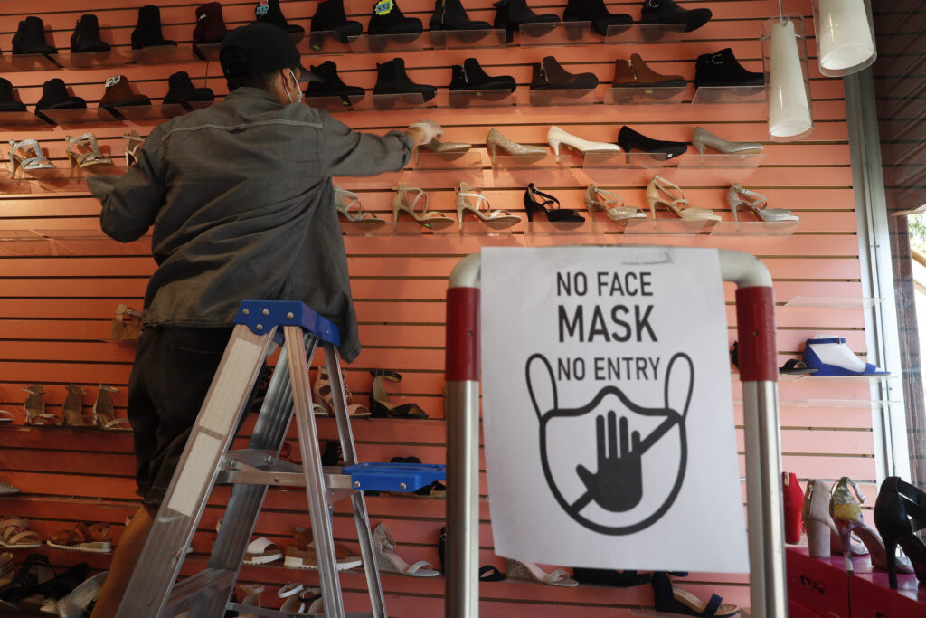Manager Angel Ramos arranges shoes on a display in Top shoes, Monday, June 8, 2020, in the Sunset Park neighborhood of the Brooklyn borough of New York, after retail stores were allowed to reopen to customers, but with some restrictions, like curbside pickup on orders, and required wearing of face coverings, as part of the state's phase one reopening plan. (AP Photo/Kathy Willens)