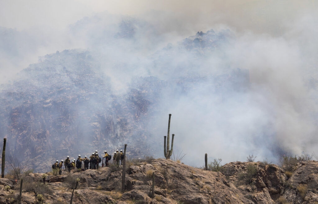A hot shot fire crew fighting the Bighorn Fire hikes on ridge in the foothills as smoke from wildfires rise in the Santa Catalina Mountains north of Tucson, Ariz., Thursday, June 11, 2020. (Rebecca Sasnett/Arizona Daily Star via AP)