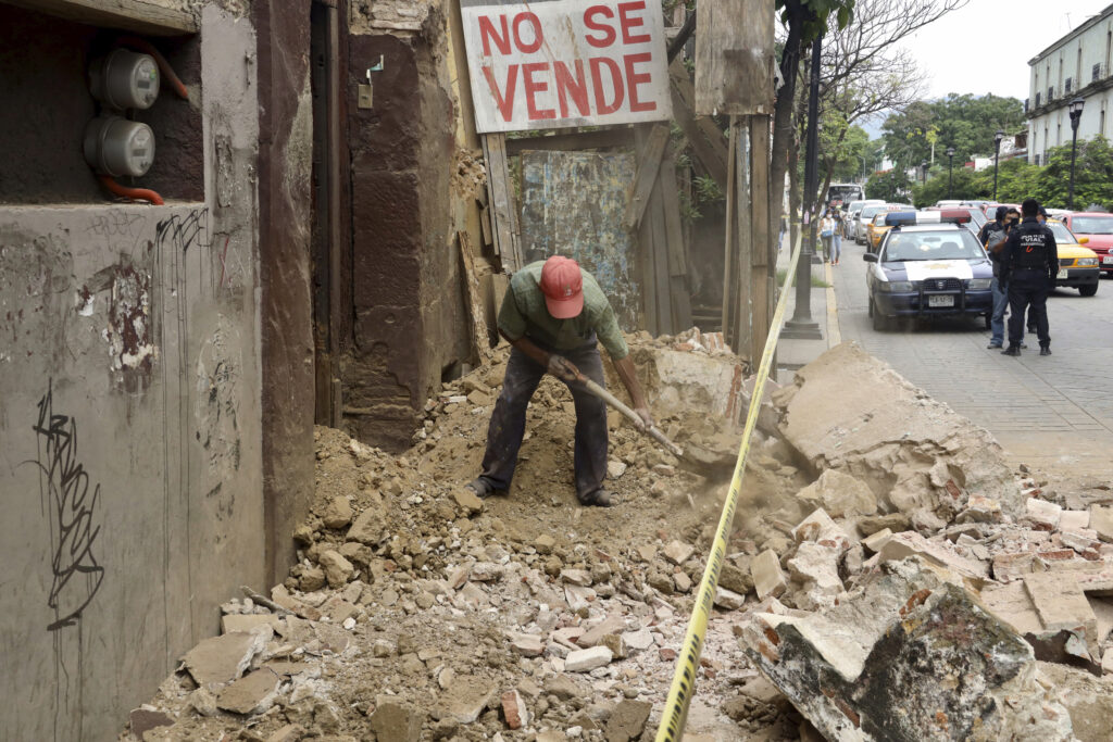 A man removes rubble from a building damaged by an earthquake in Oaxaca, Mexico, Tuesday, June 23, 2020.