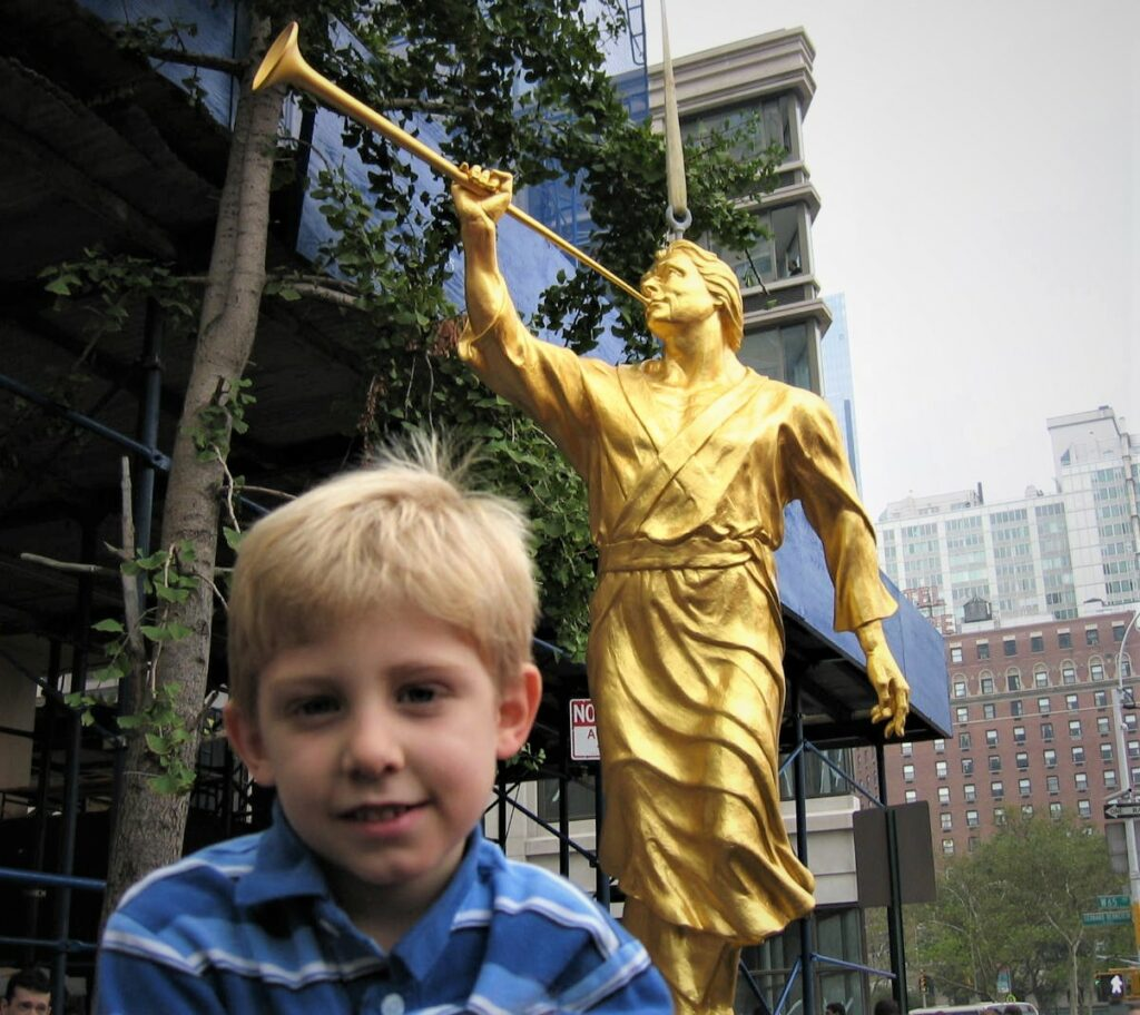 Isaac Draper in front of the Angel Moroni in New York City before it was lifted on top of the Manhattan temple. Isaac visited New York with his mother, Lori Draper.