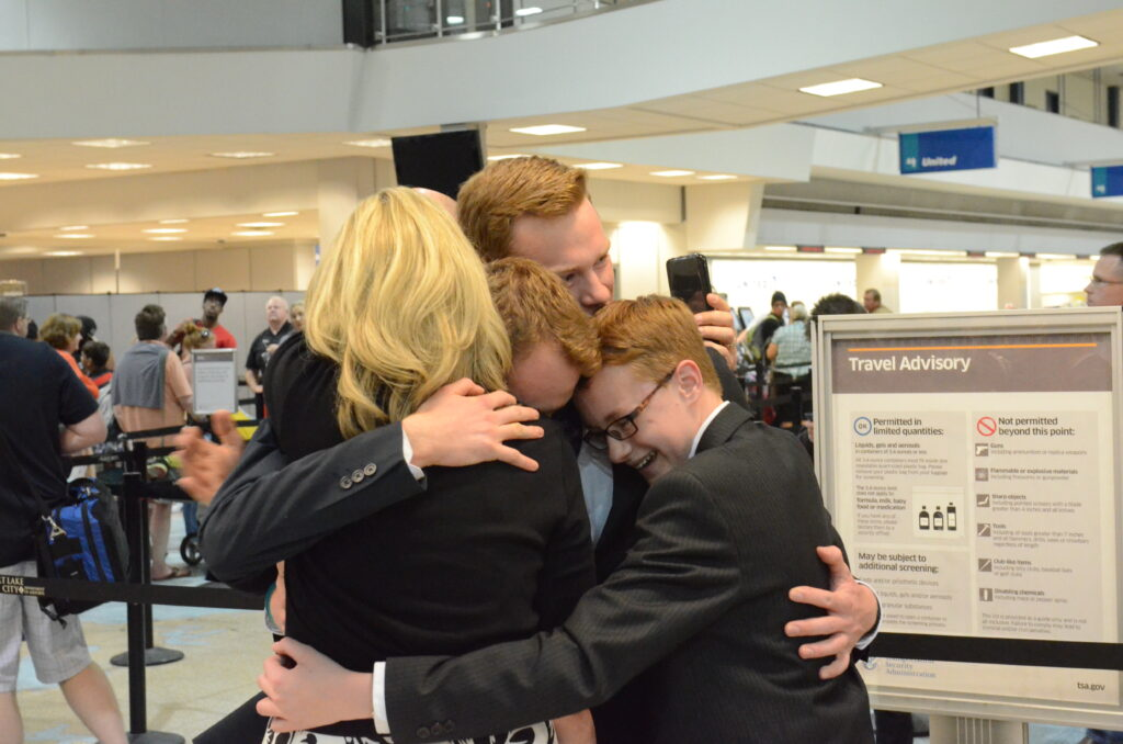 Amy Wright and some of her children embrace her oldest son at the Salt Lake City airport following his return from a mission in Italy in 2016. Amy Wright was going through cancer treatment at the time.