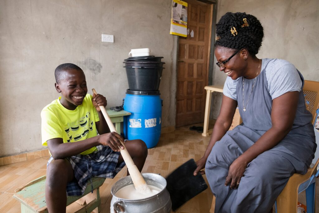 A mother helps her son prepare food. The new Children and Youth program helps children set goals to learn new skills.
