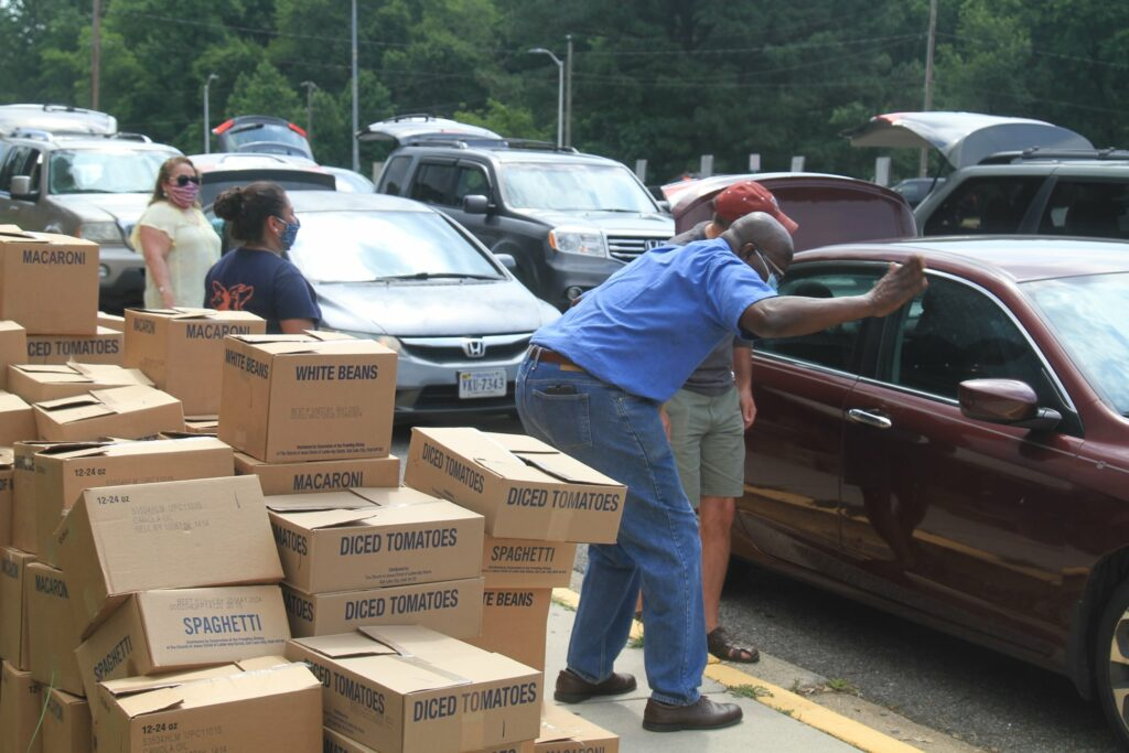 Woodbridge Virginia Stake President David Oryang, in blue shirt, greets people receiving food during stake-coordinated food drive.