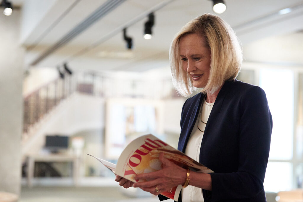 Young Women General President Bonnie H. Cordon reads a copy of the new For the Strength of Youth magazine, which will replace the New Era beginning January 2021.