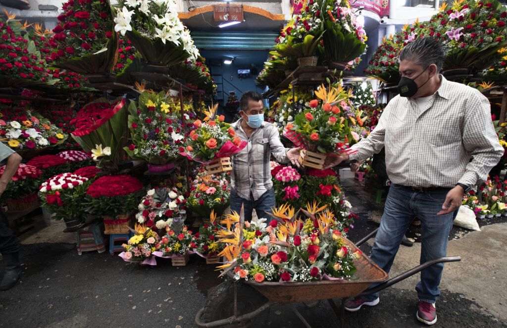 Flower merchants wearing masks to curb the spread of the new coronavirus move flower arrangements in a wheelbarrow inside Mexico City's Jamaica market, Thursday, July 30, 2020. Mexico's economic activity plummeted 18.9% in the second quarter compared to the same period last year as the economic shutdown caused by the COVID-19 pandemic drove the country deeper into a recession. (AP Photo/Marco Ugarte)