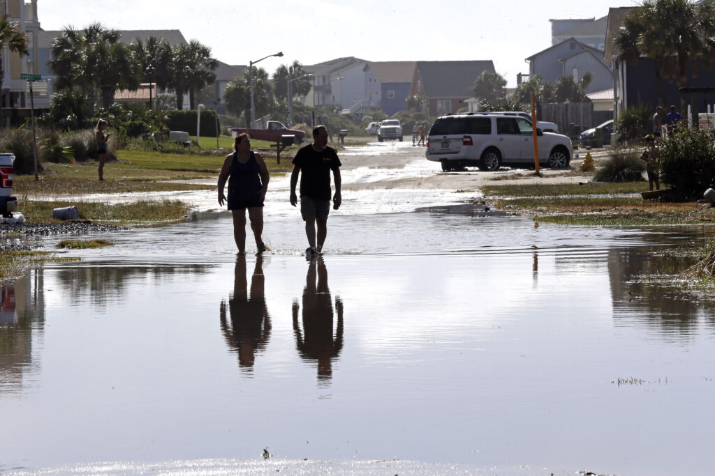 A couple walks in floodwater along Ocean Drive following the effects of Hurricane Isaias in Caswell Beach, N.C., Tuesday, Aug. 4, 2020. (AP Photo/Gerry Broome)