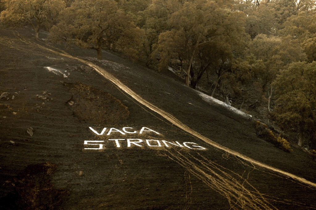 """Following the LNU Lightning Complex fires, a sign reading """"Vaca Strong"""" adorns a charred hillside in Vacaville, Calif., on Monday, Aug. 24, 2020."""
