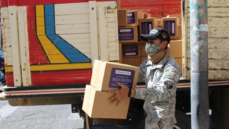 A public safety official in Bolivia unloads protective gear donated by the Church and designed to prevent the spread of COVID-19.