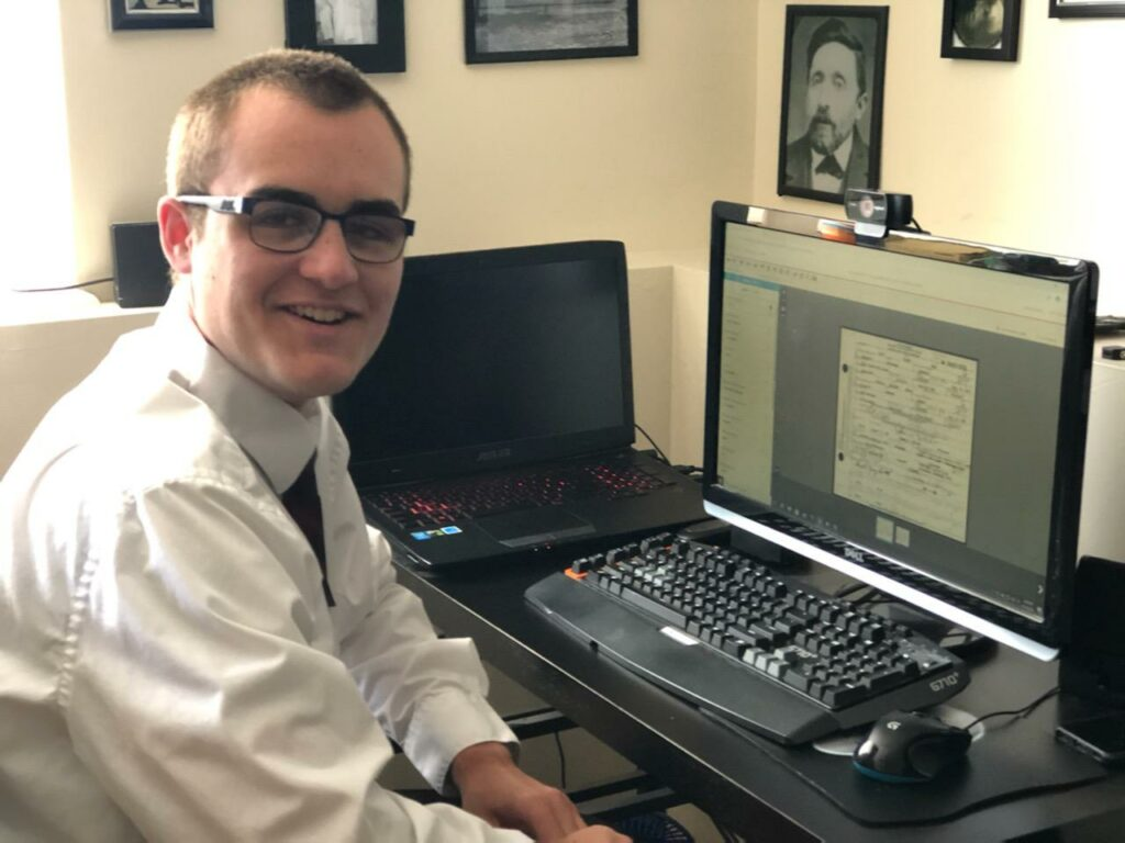 Elder Josh Scott, a Church service missionary, smiles while indexing at his home in Hebron, Kentucky, in August 2020. Elder Scott has indexed 10,100 names in six months, as of Aug. 17.