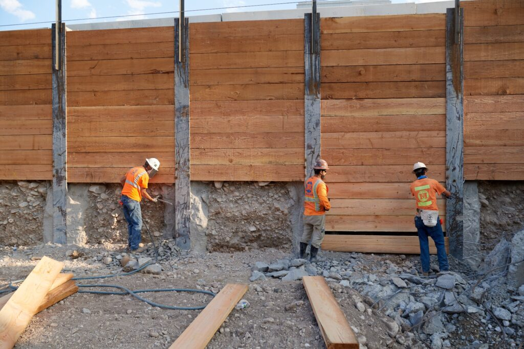 Crews install four-inch-thick wood lagging as part of a construction site retaining wall surrounding the temple grounds property. The lagging will eventually go to a depth of 40 feet after excavation is completed. A cable system helps lock the lagging in place to provide additional stability. The Salt Lake Temple renovation project, August 2020.