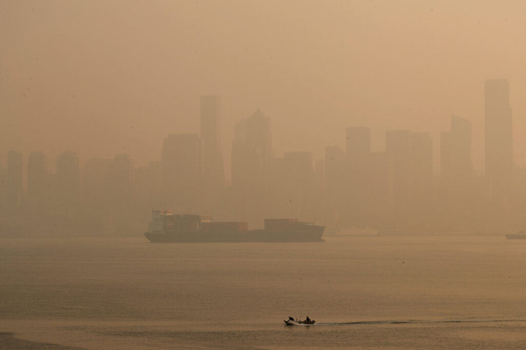 Boaters pass by the Seattle skyline during hazy air conditions Friday morning, Sept. 11, 2020. Smoke pollution from wildfires raging in California and across the Pacific Northwest worsened in San Francisco, Seattle and Portland, Oregon, on Friday, giving those cities and others in the the region some of the world's worst air quality. (Erika Schultz/The Seattle Times via AP)