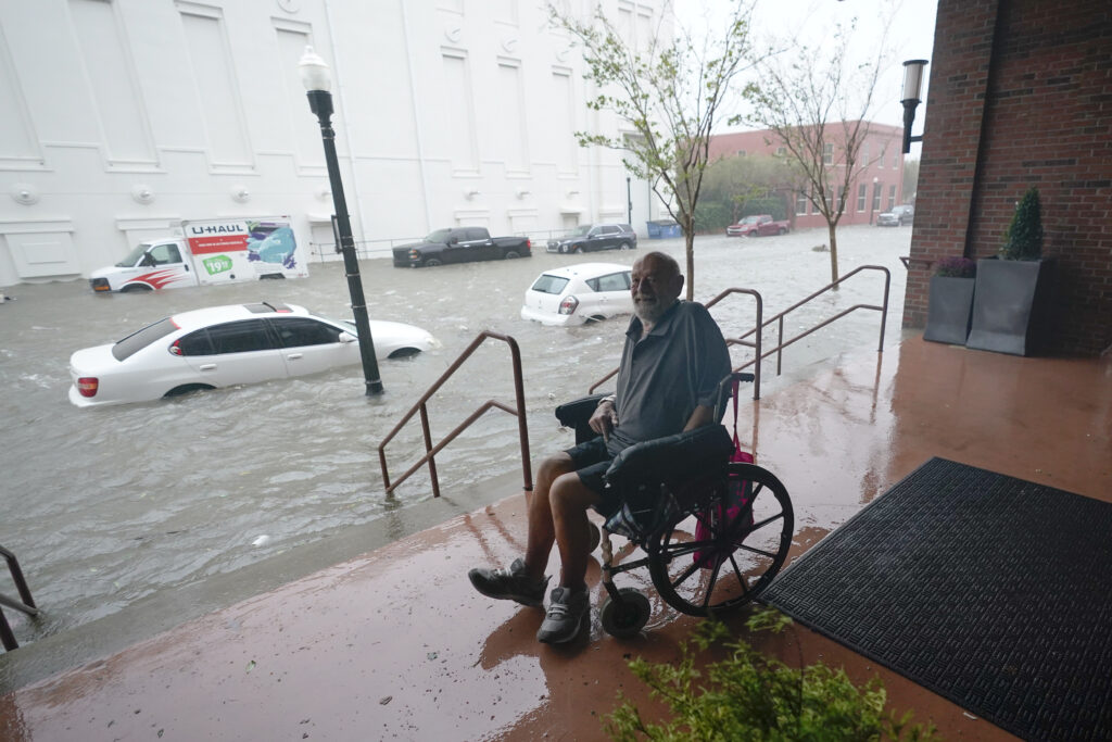 A man watches floodwaters, Wednesday, Sept. 16, 2020, in downtown Pensacola, Fla. Hurricane Sally made landfall Wednesday near Gulf Shores, Alabama, as a Category 2 storm, pushing a surge of ocean water onto the coast and dumping torrential rain that forecasters said would cause dangerous flooding from the Florida Panhandle to Mississippi and well inland in the days ahead. (AP Photo/Gerald Herbert)