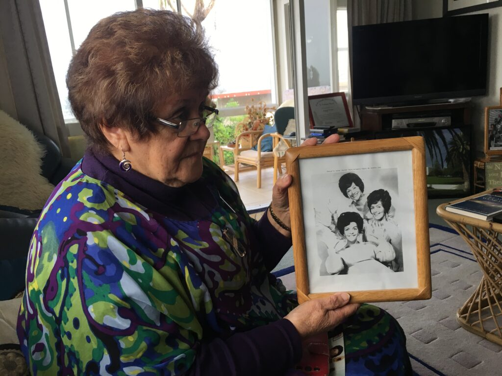 In her home in Temple View, New Zealand, Rangi Parker holds a photo