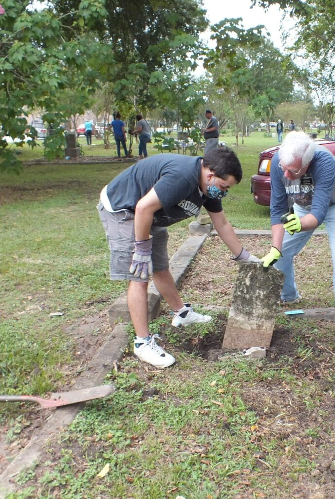 Elder Baker, left, a Church service missionary, and Elder Albert E. Haines, right, service mission leader, discover a buried headstone at the Historic Evergreen Negro Cemetery in Houston, Texas, on Saturday, Oct. 17, 2020.