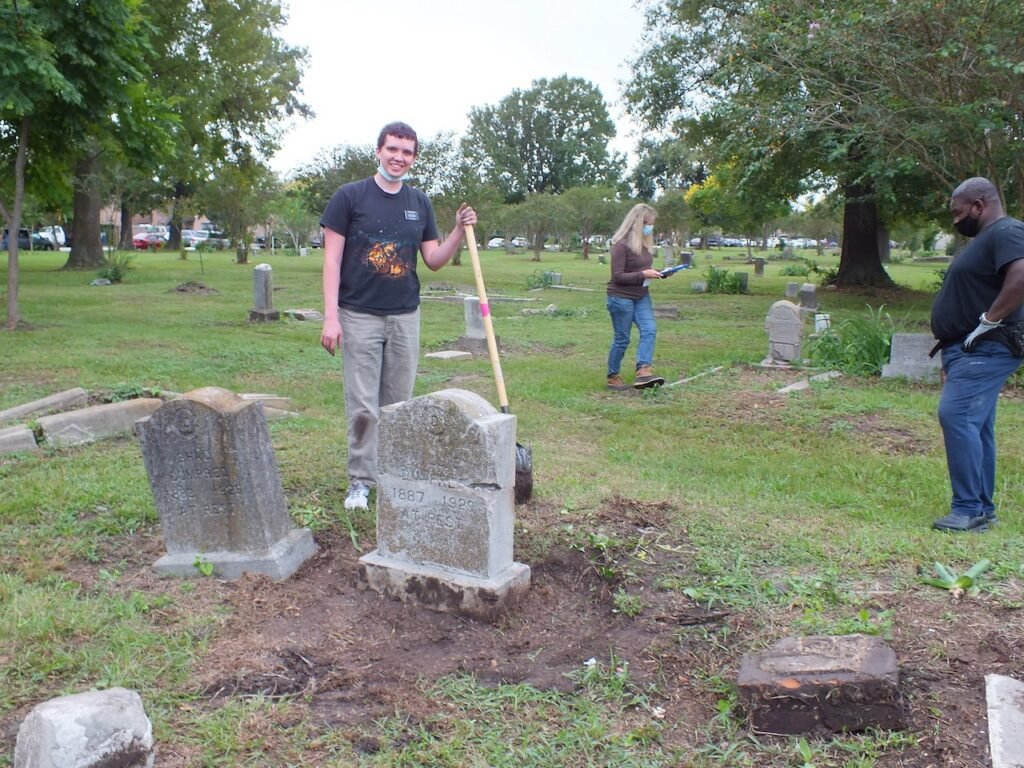 Elder Nicholas, a Church service missionary, stands next to a headstone he repaired at the Historic Evergreen Negro Cemetery in Houston, Texas, on Saturday, Oct. 17, 2020.