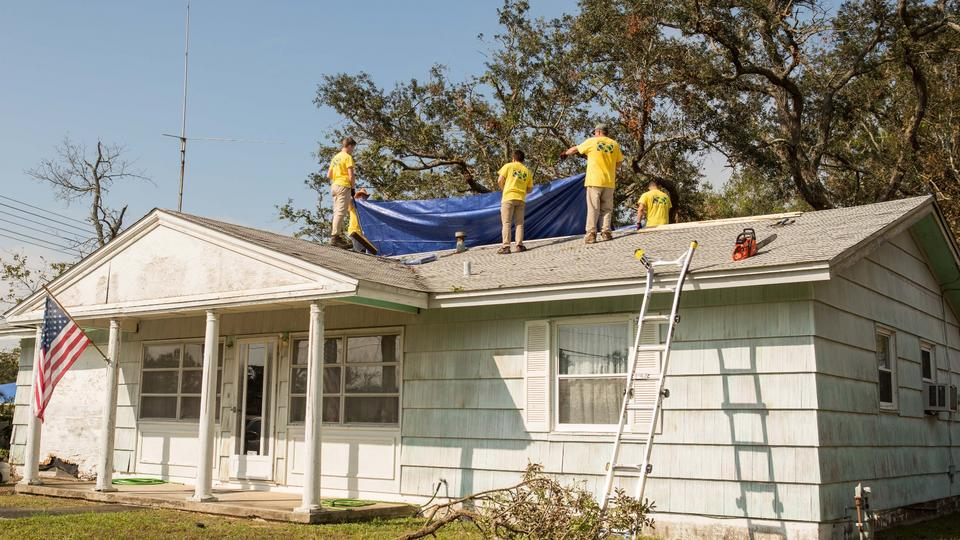 Helping Hands volunteers place a tarp on the roof of a damaged house in Pensacola, Florida, in October, 2020. A hurricane brought 100-mile-per-hour winds and millions of dollars in damage to homes and property in the region.