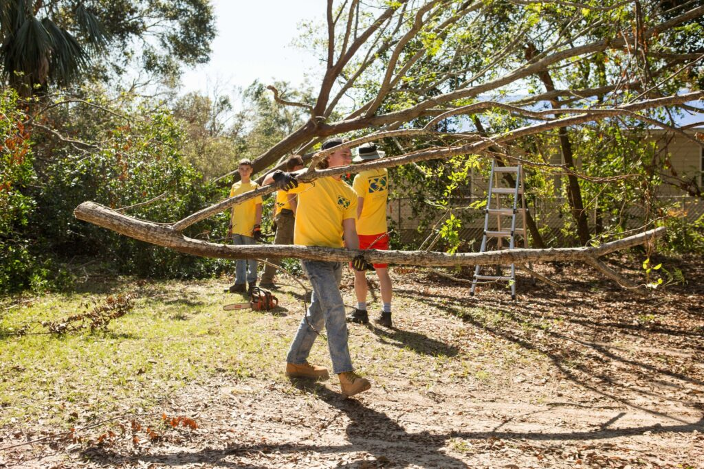 Mason Sagers of Canton, Georgia, along with other Helping Hands volunteers, help clean up debris and fallen trees caused by Hurricane Sally in Pensacola, Florida, on October 18, 2020. The Gulf Coast region was battered by violent storms during the 2020 hurricane season, prompting several Church-sponsored relief projects.