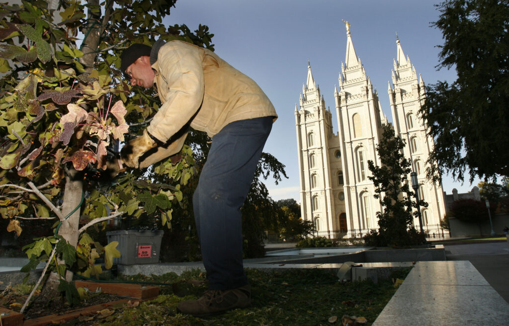 Larry Smithee hangs Christmas lights near the Church Office Building in Salt Lake City Wednesday, Oct. 26, 2011. In the background is the Salt Lake Temple.