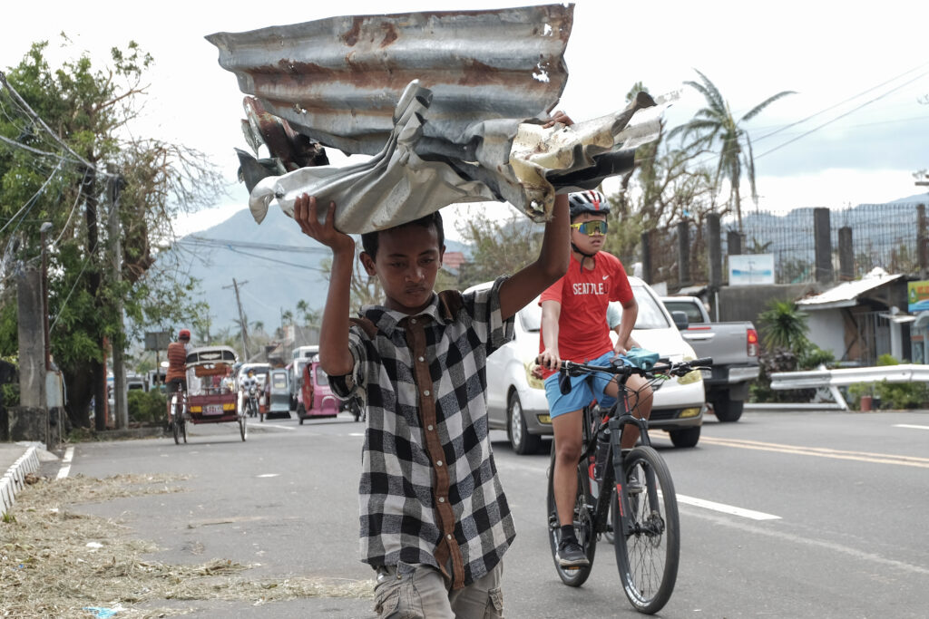 A boy carries metal sheets that were blown away from houses in the winds of Typhoon Goni in Albay province, central Philippines on Tuesday Nov. 3, 2020. More than a dozen people were killed as Typhoon Goni lashed the Philippines over the weekend, and about 13,000 shanties and houses were damaged or swept away in the eastern island province that was first hit by the ferocious storm, officials said.
