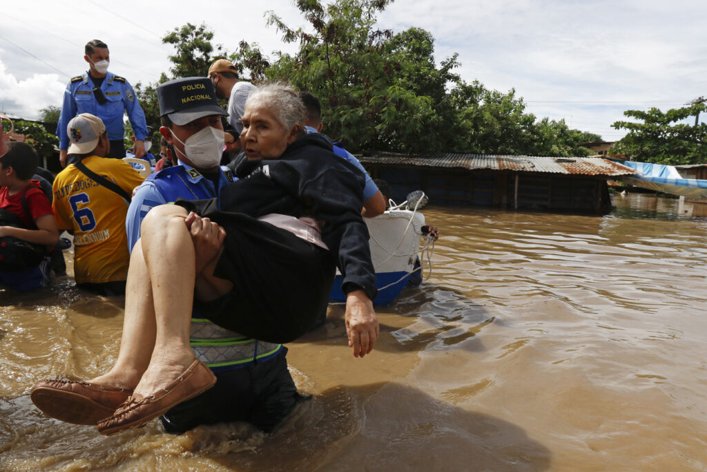 A National Police officer carries an elderly woman out of an area flooded by water brought by Hurricane Eta in Jerusalen, Honduras, Thursday, Nov. 5, 2020. The storm that hit Nicaragua as a Category 4 hurricane on Tuesday had become more of a vast tropical rainstorm, but it was advancing so slowly and dumping so much rain that much of Central America remained on high alert. (AP Photo/Delmer Martinez)