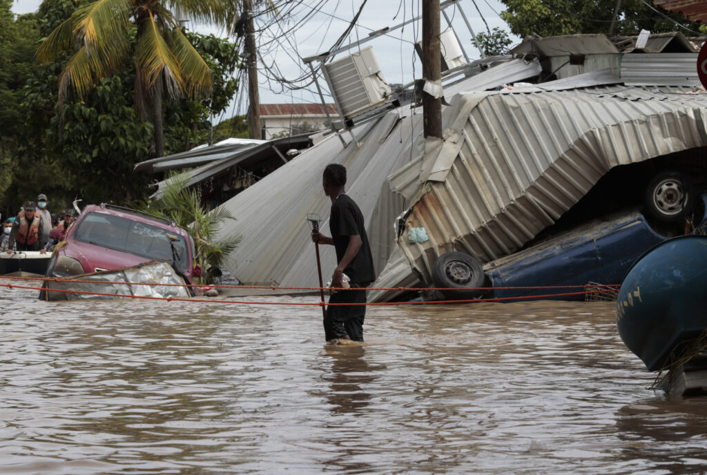 A resident walking through a flooded street looks back at storm damage caused by Hurricane Eta in Planeta, Honduras, Friday, Nov. 6, 2020. As the remnants of Eta moved back over Caribbean waters, governments in Central America worked to tally the displaced and dead, and recover bodies from landslides and flooding that claimed dozens of lives from Guatemala to Panama.