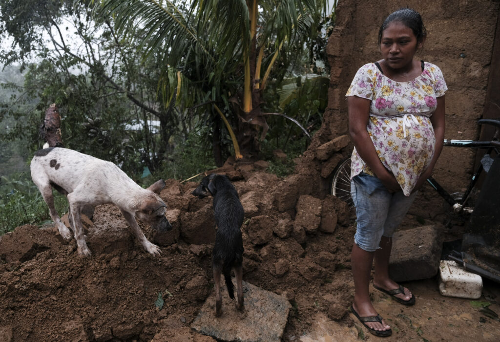 A woman stands by the fallen wall of her house after the passage of Hurricane Iota in Siuna, Nicaragua, Tuesday, Nov. 17, 2020. Hurricane Iota tore across Nicaragua on Tuesday, hours after roaring ashore as a Category 4 storm along almost exactly the same stretch of the Caribbean coast that was recently devastated by an equally powerful hurricane.