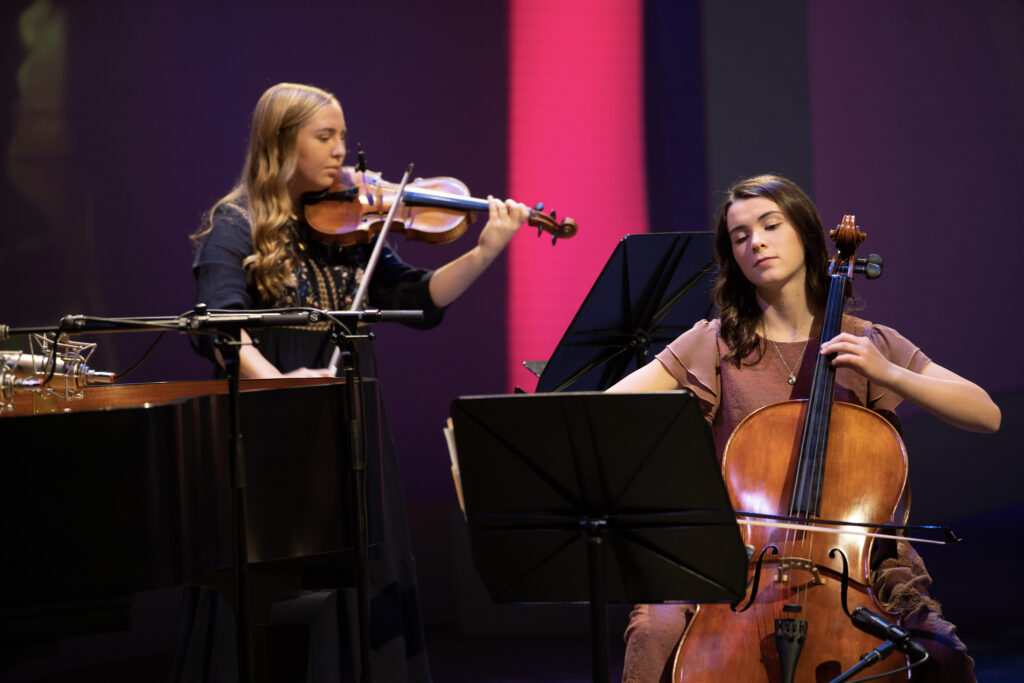 Mia Bateman and Karina Miner play musical instruments on Sunday, November 15, 2020, as part of the Face to Face broadcast for young women that celebrates 150 years since the Church organization for that age group met for the first time. Before the event, the Young Women General Presidency invited current and previous members of the young women organization to share how their leaders blessed their lives on social media.