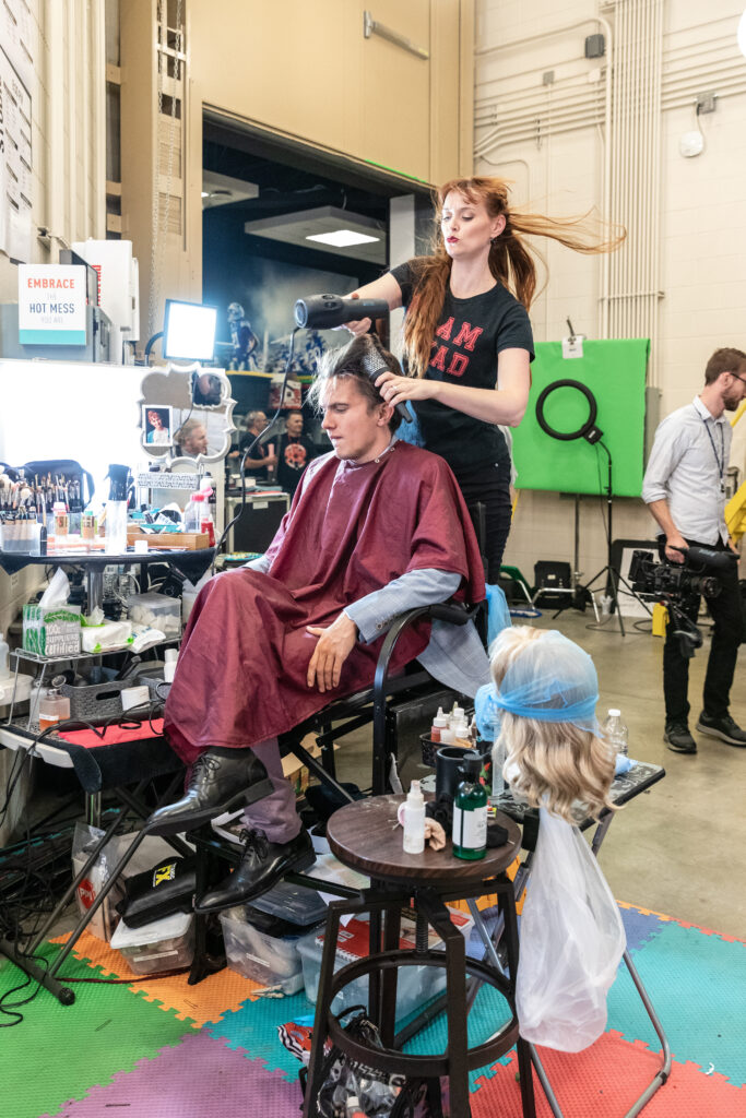 """A crew member gets """"Studio C"""" cast member Tanner Gillman ready for an upcoming sketch. The series' 12th season is currently airing Monday nights on BYUtv. Season 13 will premiere in 2021."""