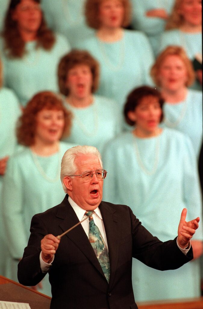 Jerold Ottley conducts the audience during a session of general conference.