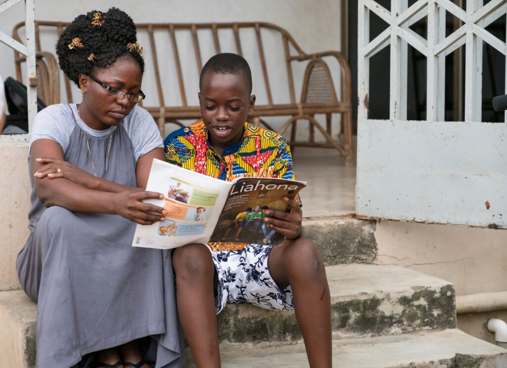 A mother and her son in Ghana read the Liahona. Starting in January 2021 there will be three global magazines: the Liahona for adults, For the Strength of Youth for teenagers and the Friend for children.