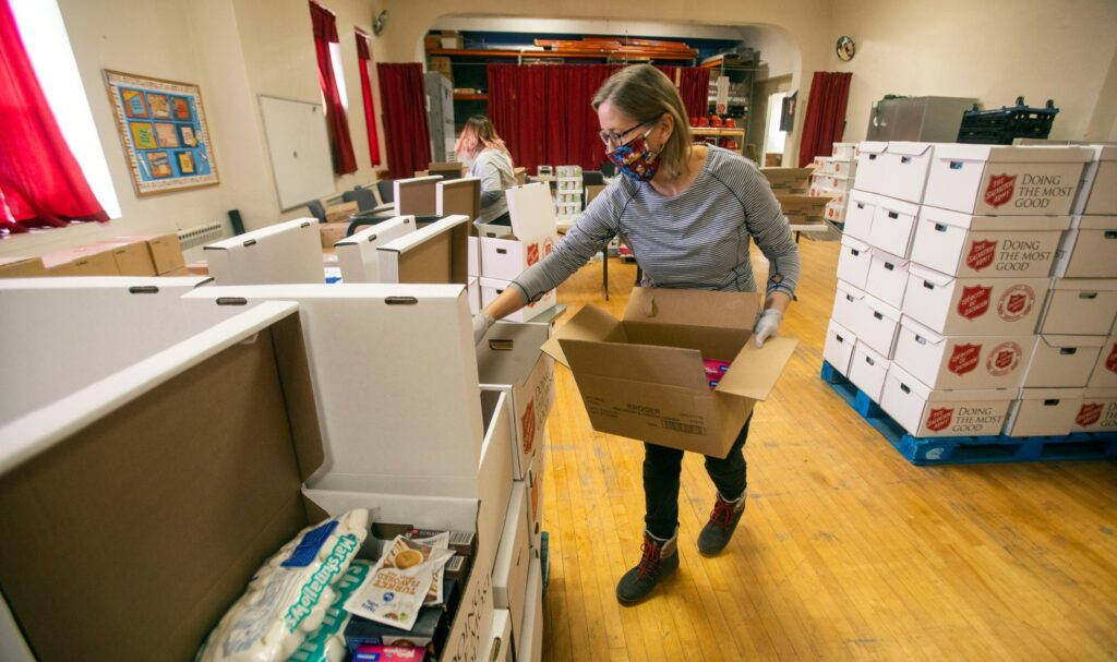 A volunteer helps pack food at the local Salvation Army in Salt Lake City on Tuesday, Dec. 15, 2020. The April and December donations represent 52,000 food boxes, each of which feeds four to five people for several meals.