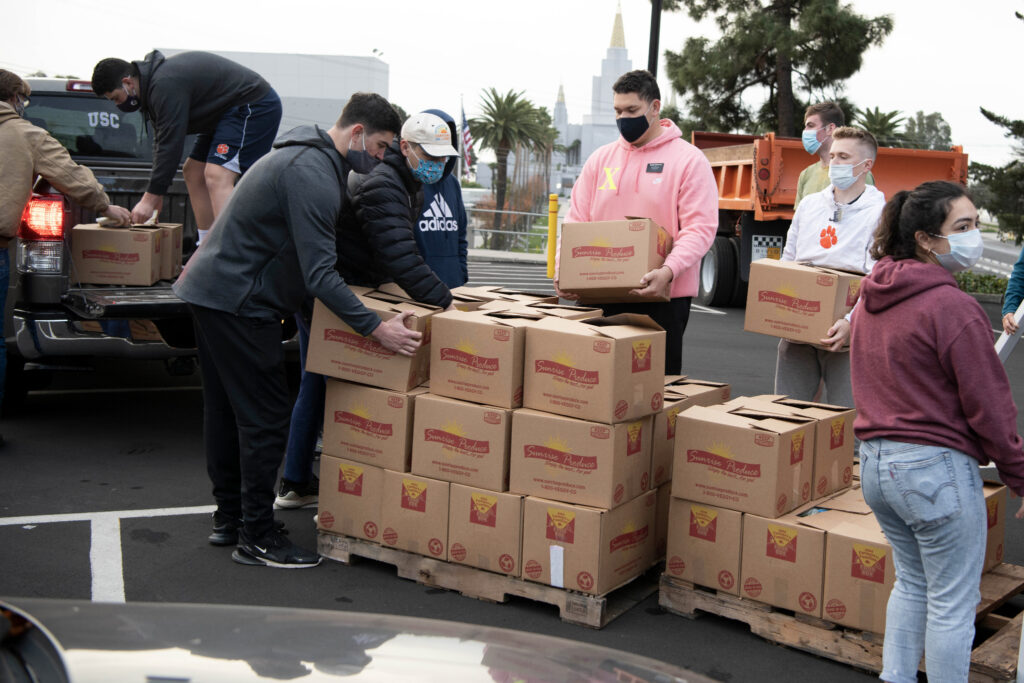 Latter-day Saint missionaries move USDA Farmers to Families Food Box Program boxes from pallets to the back of a vehicle on Friday, Dec. 11, 2020, in Oakland, California. Church members from Oakland and San Francisco congregations also participated.
