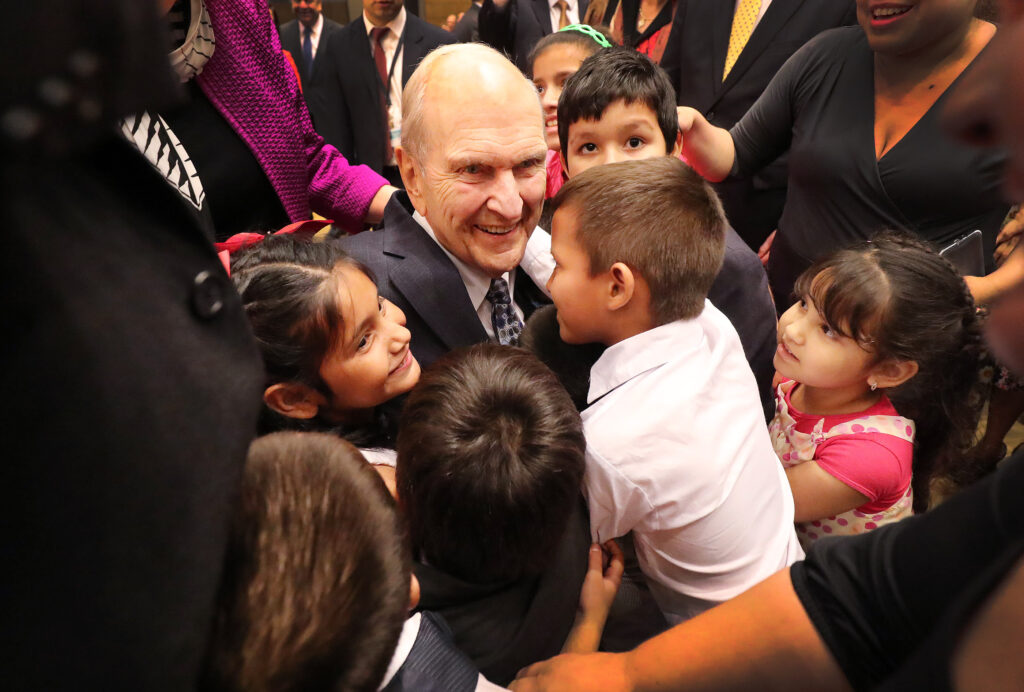 President Russell M. Nelson of The Church of Jesus Christ of Latter-day Saints hugs children after a devotional in Asunción, Paraguay, on Monday, Oct. 22, 2018.