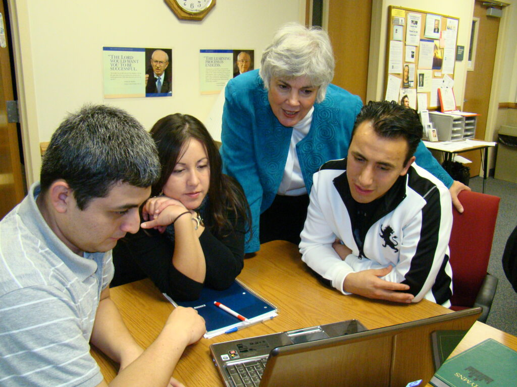 Pathway students enrolled in an online learning program work with a Church service missionary at New York Institute Building in 2017.