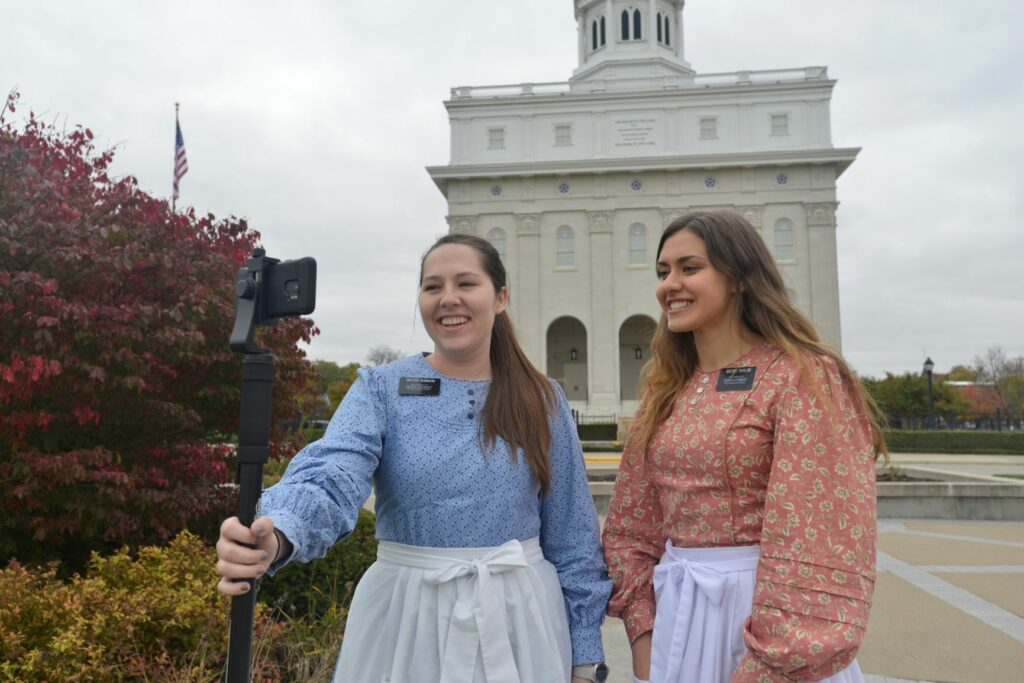 Sister Karly Robison and Sister Meg Taylor, missionaries serving at the Nauvoo historic sites, give a virtual tour in front of the Nauvoo Illinois Temple. Because of the COVID-19 pandemic, Church historic sites have been closed since March 2020.