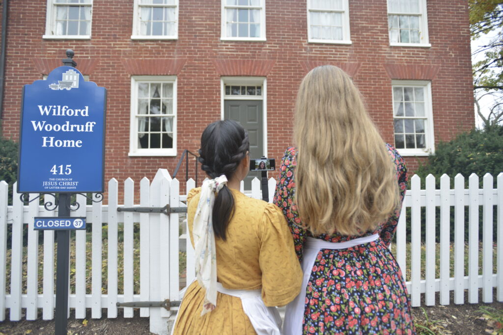 Sister Daicee Smuin and Sister Sheila Cabuquing, missionaries serving at the Nauvoo Historic Sites, stop to show virtual visitors the Wilford Woodruff home in Nauvoo. Because of COVID-19, Church historic sites have been closed to in-person visitors since March 2020.