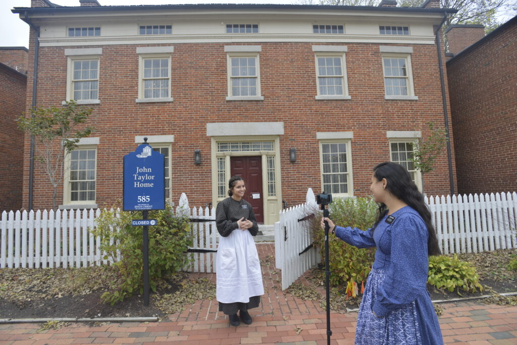 Sister Bailee Edwards-Kevin and Sister Melissa Froes, missionaries serving at the Nauvoo Historic Sites, stop to show virtual visitors the John Taylor home in Nauvoo. Because of COVID-19, Church historic sites have been closed to in-person visitors since March 2020.
