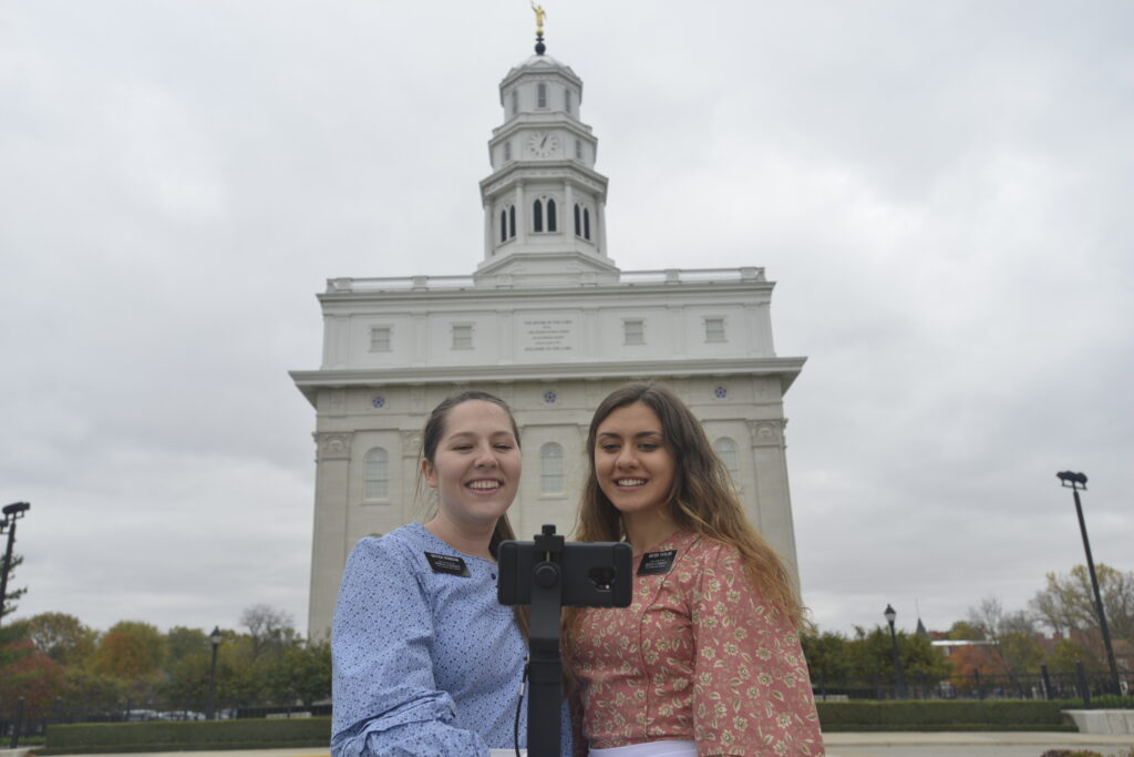 Sister Karly Robison and Sister Meg Taylor, missionaries serving at the Nauvoo Historic Sites, give a virtual tour in front of the Nauvoo Illinois Temple. Because of COVID-19, Church historic sites have been closed since March 2020.