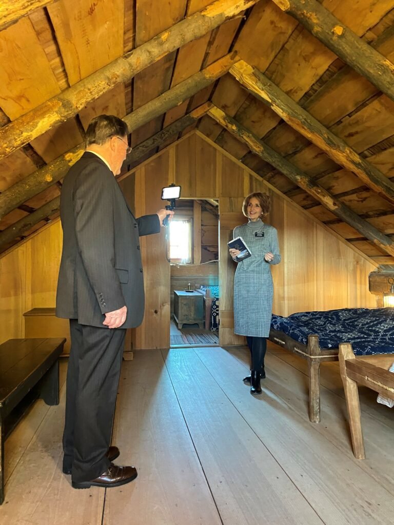 Elder Lynne Pettit and Sister Lanette Pettit give a virtual tour in the upstairs of the Smith Log Home at the New York historic site.